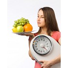 Young woman holding a weight scale and plate with fresh fruit