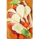Sliced prosciutto and mozzarella with basil and tomatoes