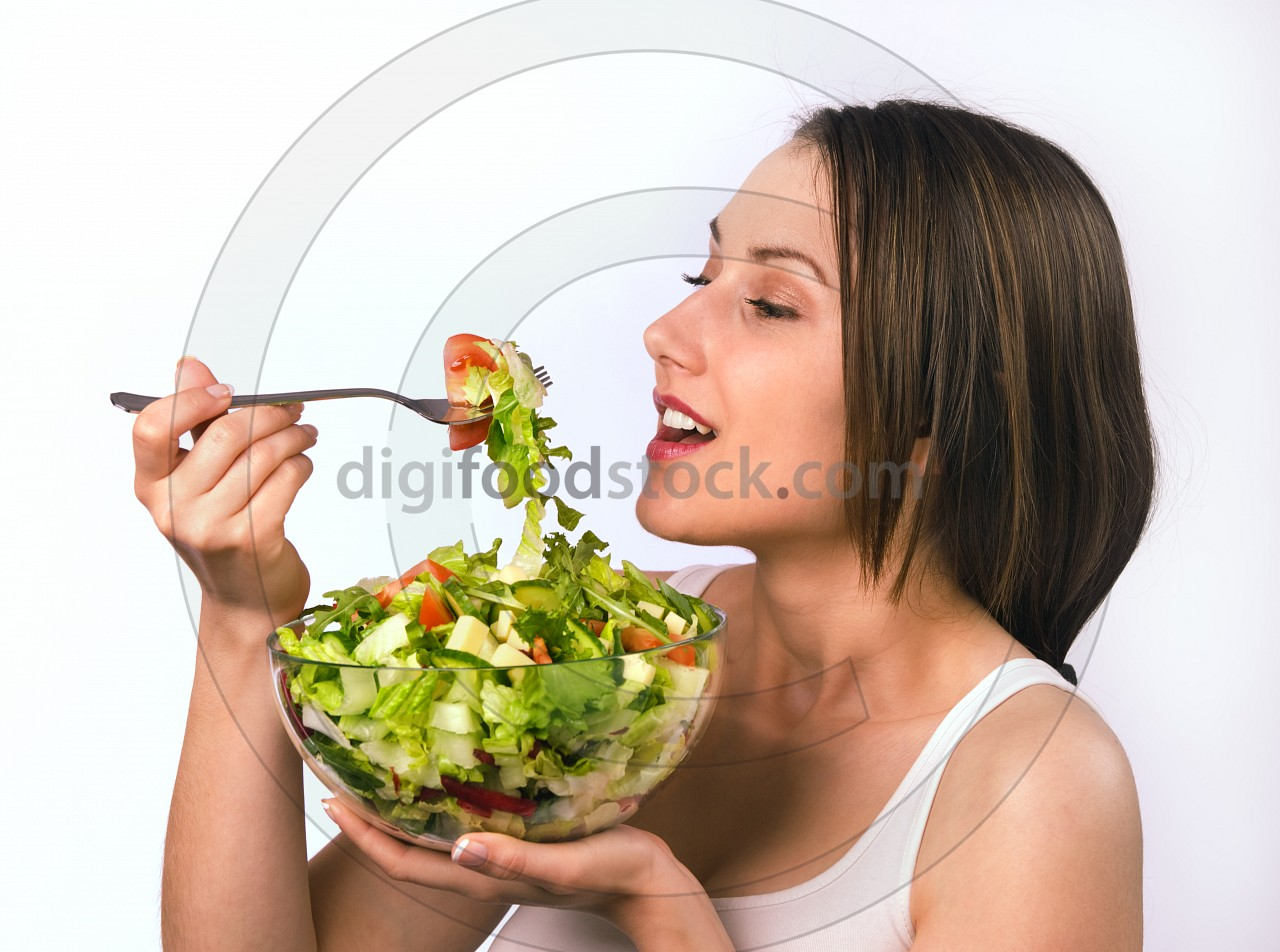 Young woman eating healthy salad