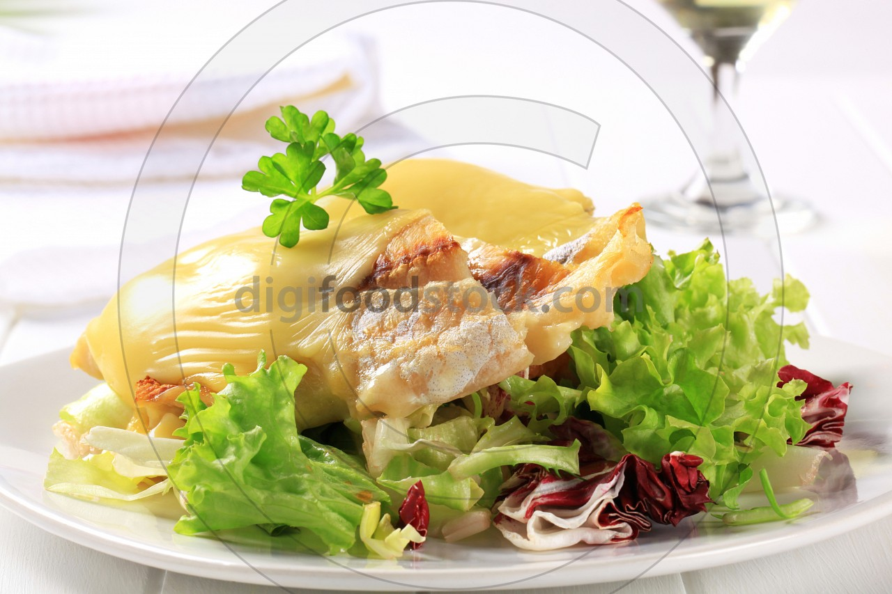Cheese topped fish fillets with salad