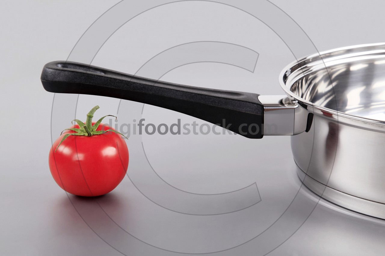 Shiny saucepan and red tomato
